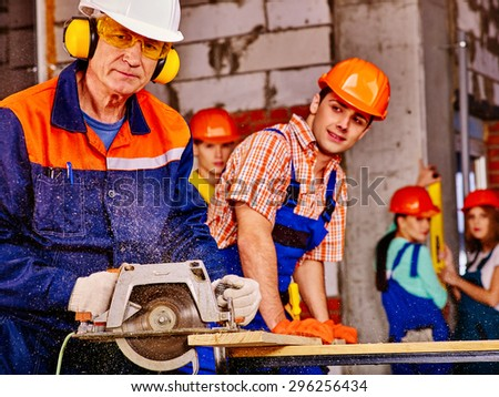 Happy group people  and old man builder with circular saw. Brick wall in background. - stock photo