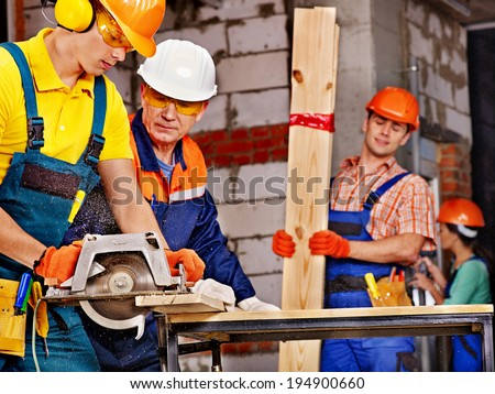 Happy group people  builder with circular saw. - stock photo