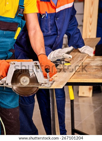 Happy group people  builder with circular saw.
