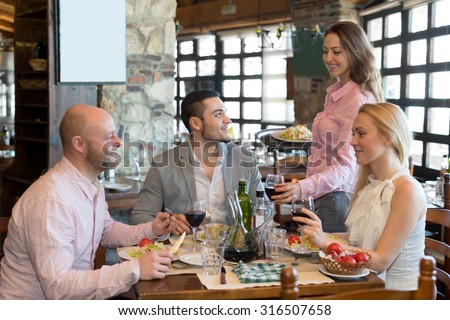 Happy group people having dinner at rural restaurant and drinking wine. Focus on the young man - stock photo