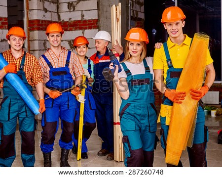 Happy group people men and women in builder uniform. - stock photo