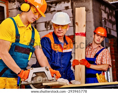 Happy group people  of three people builder with circular saw. - stock photo