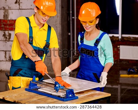 Happy group people of two person builder cutting ceramic tile. - stock photo