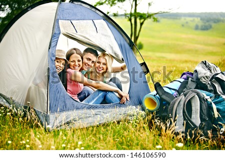 Happy group people with backpack in tent summer outdoor.
