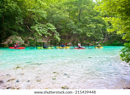 Happy group traveling by kayak on the green waters of Acheron river in Greece. - stock photo