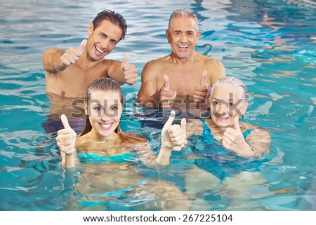 Happy group with senior couple in water holding their thumbs up - stock photo