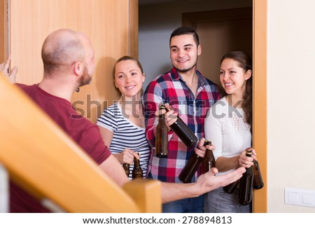 Happy guests with bottles standing in doorway and smiling for party