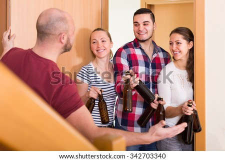 Happy guests with bottles standing in doorway and smiling in house
