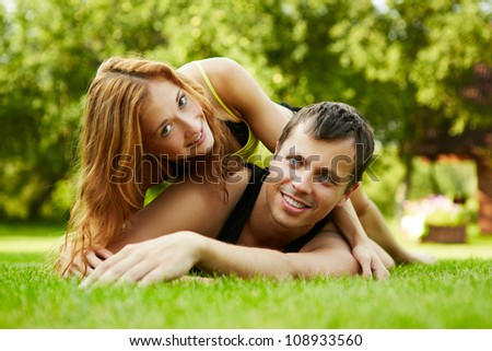 Happy guy and the girl on a grass - stock photo