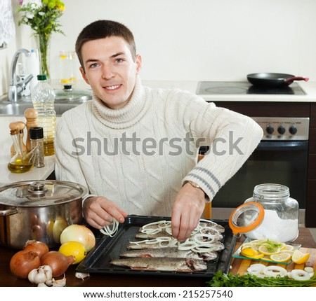 Happy guy cooking trout fish with onion in baking sheet at home kitchen  - stock photo