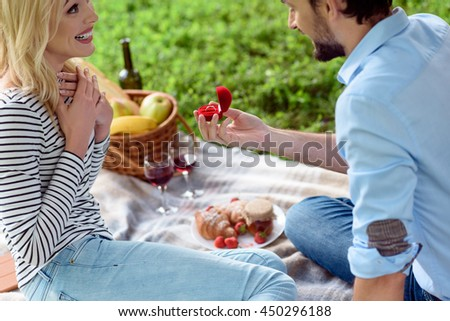 Happy guy is proposing marriage to girlfriend - stock photo