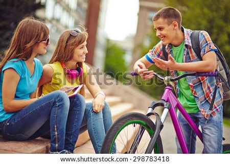 Happy guy on bicycle talking to pretty girls outside - stock photo