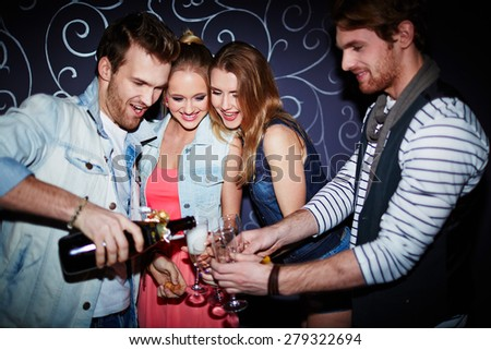 Happy guy pouring champagne in flutes of friends at party - stock photo