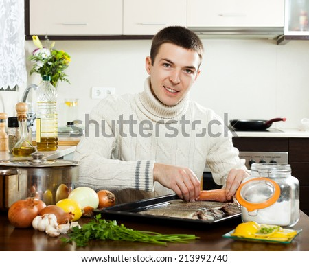Happy guy putting  saltwater fish into sheet pan at kitchen table - stock photo