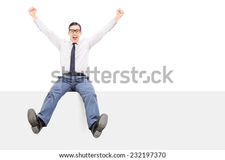 Happy guy sitting on a panel and throwing his hand in the air isolated on white background - stock photo