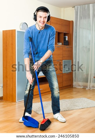 Happy guy   sweeping the floor in  home - stock photo
