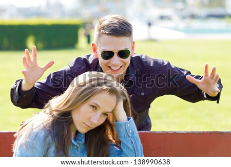 Happy guy trying to surprise her thoughtful girlfriend - stock photo