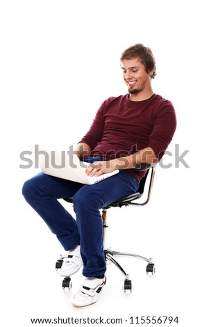 Happy guy with laptop sitting in the chair over white background - stock photo