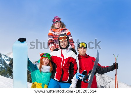 Happy guys standing with snowboards and skis