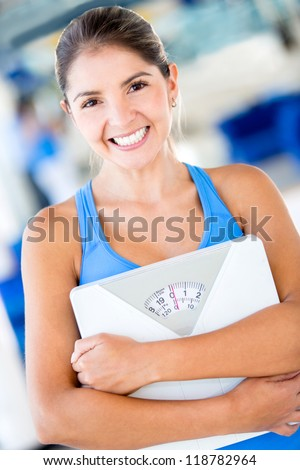 Happy gym woman holding weight scale - stock photo