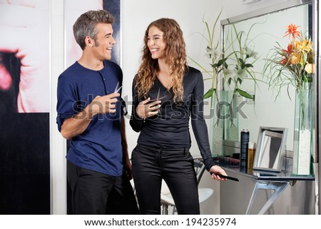 Happy hairdressers looking at each other while holding scissors in salon - stock photo
