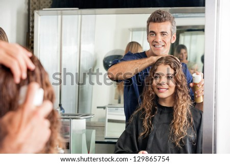 Happy hairstylist setting up client's hair while looking at mirror in salon - stock photo
