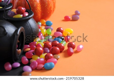 Happy Halloween candy in trick or treat carry cauldrons with witches hat on orange background. Close up with copy space. - stock photo