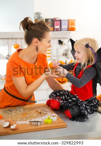 Happy halloween dressed girl with mother holding uncooked biscuits in decorated kitchen. Halloween treats ready to go into oven. Traditional autumn holiday.