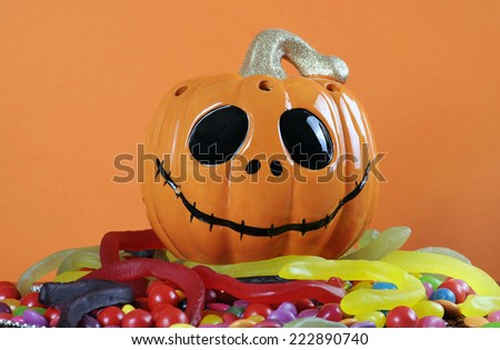 Happy Halloween Jack-o-Lantern pumpkin with colorful trick or treat candy jellies, orange chocolates, and snakes against an orange background. - stock photo