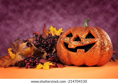 Happy Halloween orange glitter jack-o-lantern pumpkin with autumn leaves and berries against a bright modern colorful dark pink and orange background. - stock photo