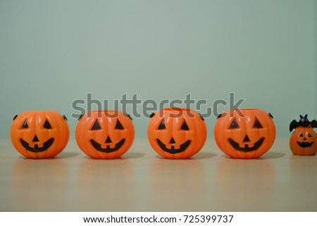 Happy Halloween party, bowl of sweet candy, orange plastic pumpkin for candies on wooden table, trick or treat