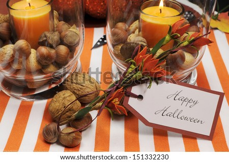 Happy Halloween tag message with orange candles and nuts centerpieces with pumpkin jack o lantern decorations. - stock photo