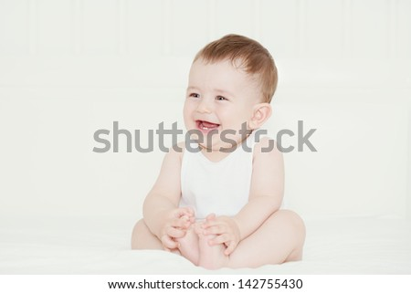 Happy handsome baby boy laughing and showing his first teeth - stock photo