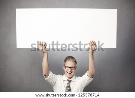 Happy handsome businessman holding white blank horizontal billboard with space for text isolated on grey background. - stock photo
