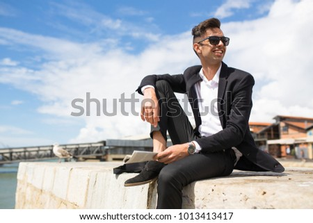 Happy handsome businessman relaxing on pier