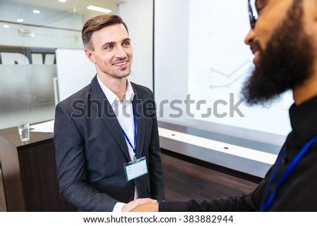 Happy handsome businessman shaking hands with young bearded african american colleague in office - stock photo
