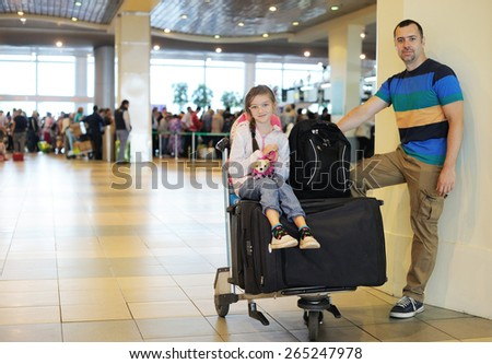 Happy handsome  father and daughter with the luggage at airport - stock photo