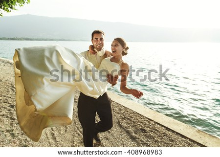 Happy handsome groom holding bride in his arms on beach at sunset