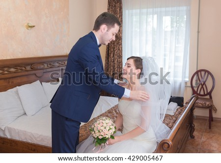 Happy handsome groom with bouquet entering room
