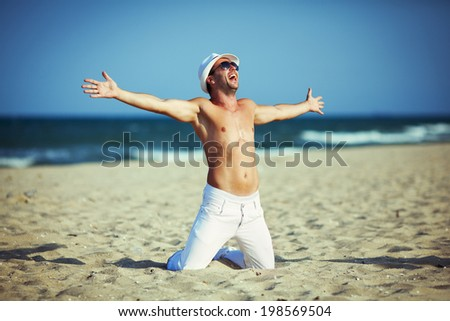 Happy handsome guy in sunglasses sitting on sand beach with hands stretched
