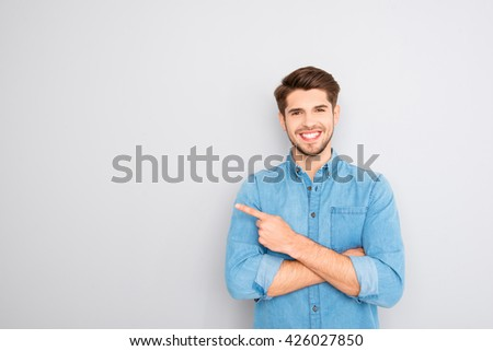 Happy handsome guy showing way and pointing with finger - stock photo