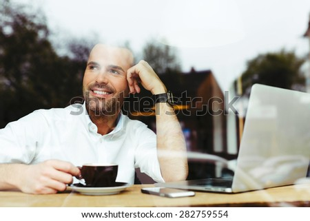 Happy handsome man at cafe drinking coffee and looking out the window - stock photo