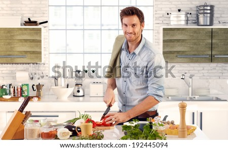 Happy handsome man cooking in kitchen at home. - stock photo