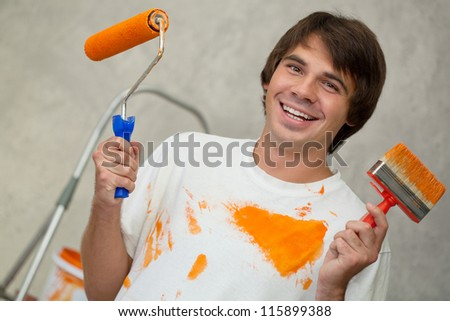 Happy handsome man in dirty t-shirt  holding paintbrushes - stock photo