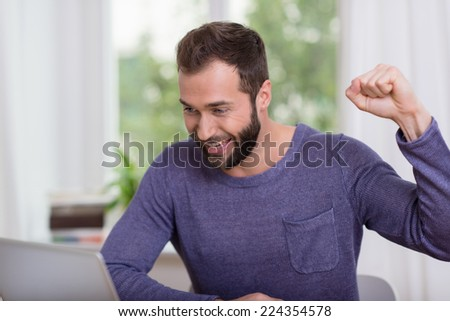 Happy Handsome Man in Long Sleeve Shirt Reading Good News at Laptop - stock photo
