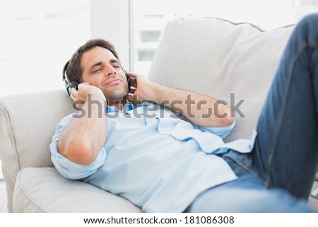 Happy handsome man lying on sofa listening to music at home in the living room