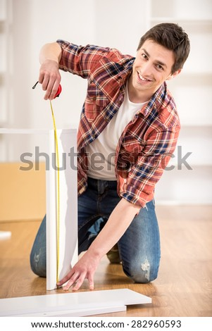 Happy handsome man measuring home furniture with measure tape. Repair concept.