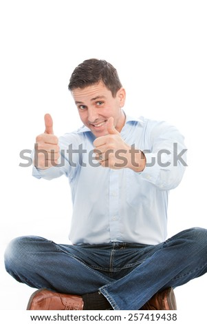 happy Handsome Man Sitting on the Floor with Crossed Legs Showing Two Thumbs up Signs at the Camera. Isolated on White Background.