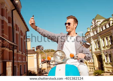 Happy handsome man sitting on the scooter making selfie photo - stock photo