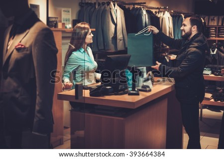 Happy handsome man taking shopping bag from saleswoman in a suit shop. - stock photo